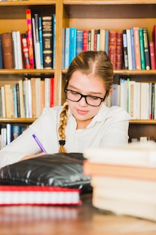 Girl writing sitting at library desk