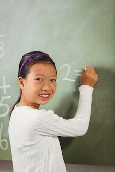 Girl writing with chalk on blackboard