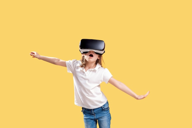 Girl  y.o in formal outfit wearing vr glasses putting hands out in excitement isolated on yellow . child using a gaming gadget for virtual reality. virtual technology