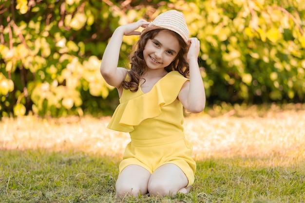 Girl in yellow clothes and hat sits on the grass in the park in summer. high quality photo