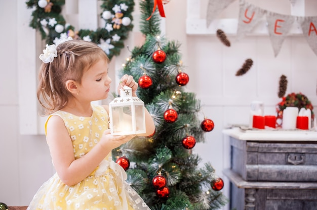 Girl in yellow dress in front of tree holds the christmas lantern