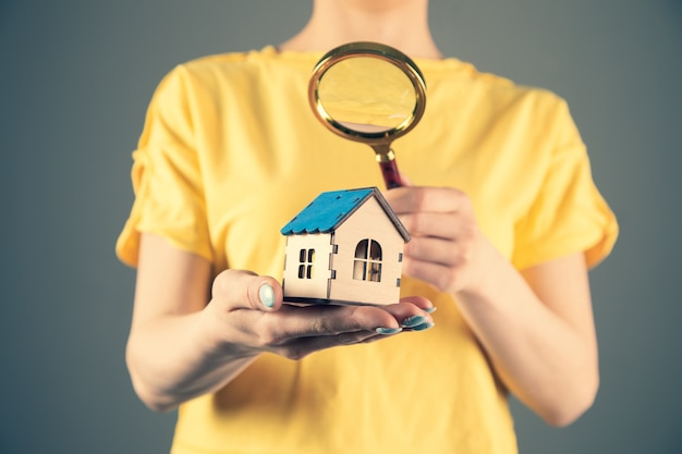 Girl in a yellow dress holds a magnifying glass and a house. home search concept