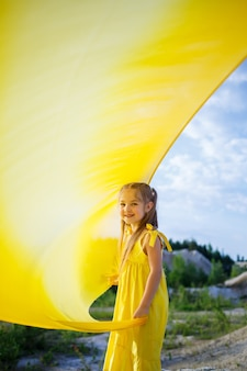 Girl in a yellow dress with wings in a yellow cloth near the lake