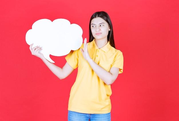 Ragazza in codice di abbigliamento giallo che tiene una scheda informativa a forma di nuvola e ferma qualcosa.