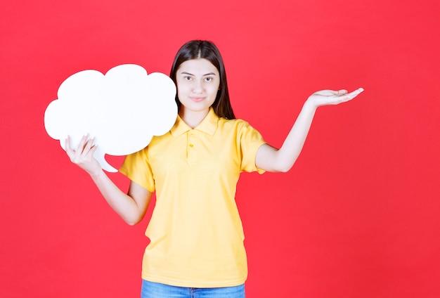 Ragazza in codice di abbigliamento giallo con in mano una bacheca informativa a forma di nuvola