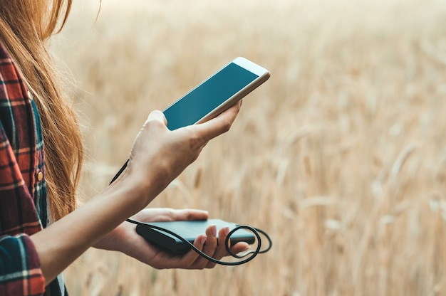 Girl in a yellow field holding a phone in her hand, and charging it from power bank.