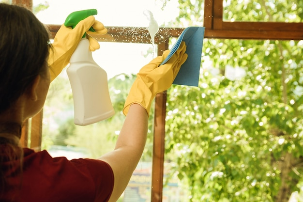 Girl in yellow gloves with a detergent washes plastic windows. cleaning company for home and window cleaning