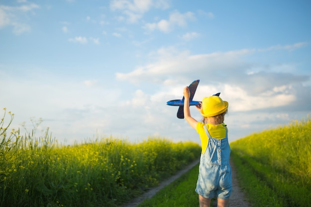 Girl in a yellow hat launches a toy plane into the field, looks at the trail. summer time, childhood, dreams and carelessness. air tour from a travel agency on a trip, adventure and vacation.
