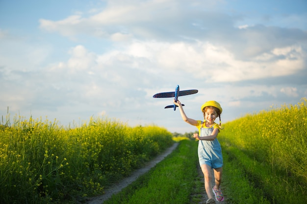Girl in a yellow panama hat launches a toy plane into the field. summer time, childhood, dreams and carelessness. air tour from a travel agency on a trip, adventure and vacation. village, cottage core Premium Photo