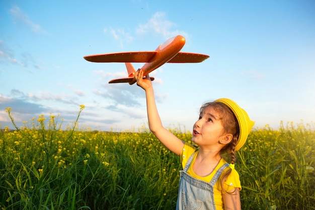 Girl in a yellow panama hat launches a toy plane into the field. summer time, childhood, dreams and carelessness. air tour from a travel agency on a trip, adventure and vacation. village, cottage core