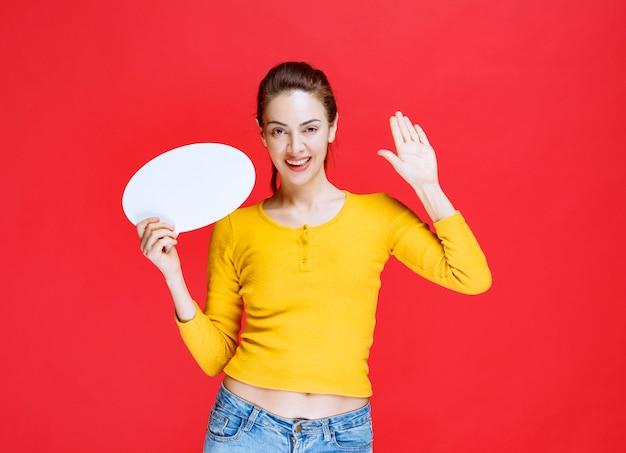 Ragazza in camicia gialla che tiene in mano un pannello informativo ovale e saluta qualcuno