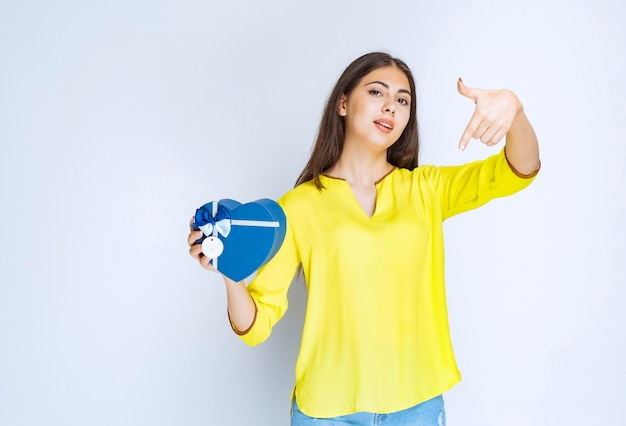 Ragazza in camicia gialla che tiene e promuove una confezione regalo a forma di cuore blu.