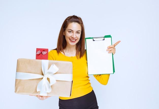 Ragazza in camicia gialla che tiene un rosso e scatole regalo di cartone e chiede una firma.