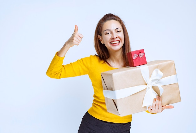 Girl in yellow shirt holding a red and a cardboard gift boxes and showing positive hand sign.