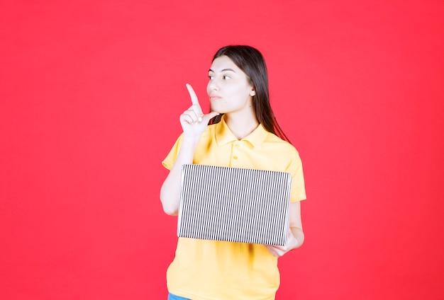 Ragazza in camicia gialla che tiene in mano una scatola regalo d'argento e sembra confusa e pensierosa