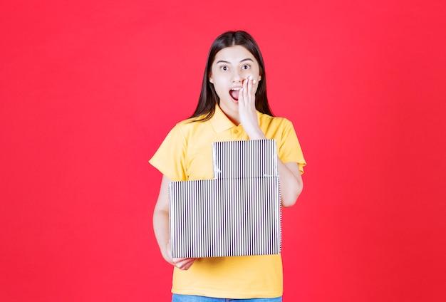 Ragazza in camicia gialla che tiene in mano una scatola regalo d'argento e sembra eccitata e sorpresa