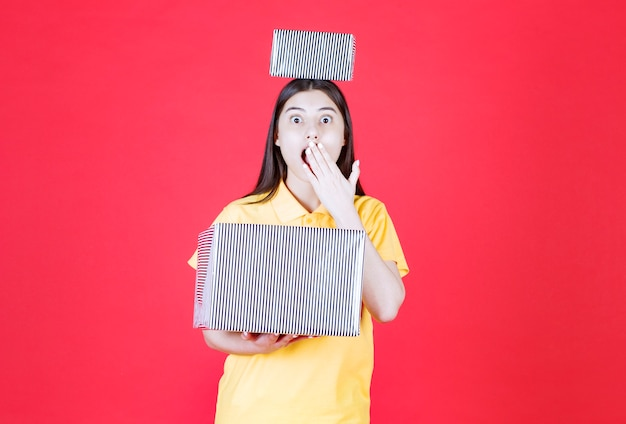 Ragazza in camicia gialla che tiene in mano una scatola regalo d'argento e sembra spaventata e terrorizzata