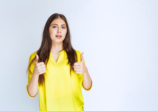 Girl in yellow shirt showing thumb up sign.