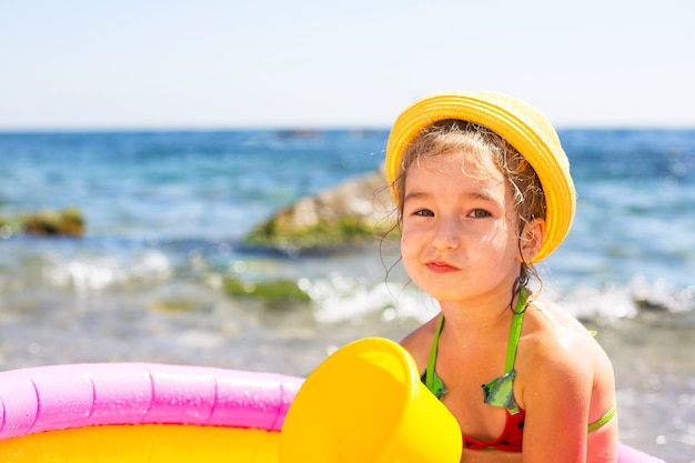 Girl in yellow straw hat sitting in an inflatable pool by the sea with a serious and dissatisfied look. indelible products to protect children's skin from the sun, sunburn. resort at the sea.