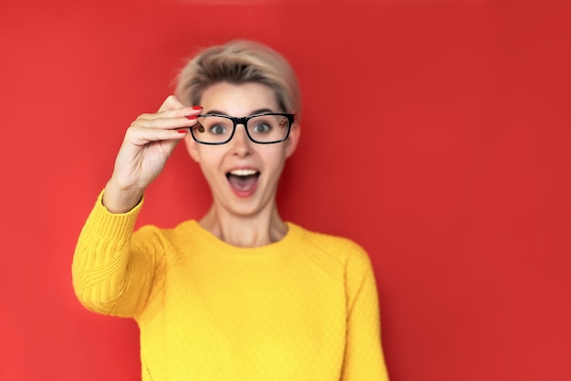 A girl in a yellow sweater looks through glasses