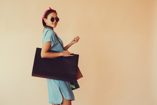 Girl on a yellow wall with shopping bags