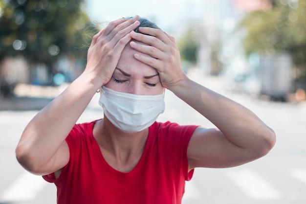 Девушка, молодая европейская женщина в защитной стерильной медицинской маске на лице страдает от головной боли, держа голову руками. симптомы вируса, китайская концепция пандемического коронавируса. 2019 нков