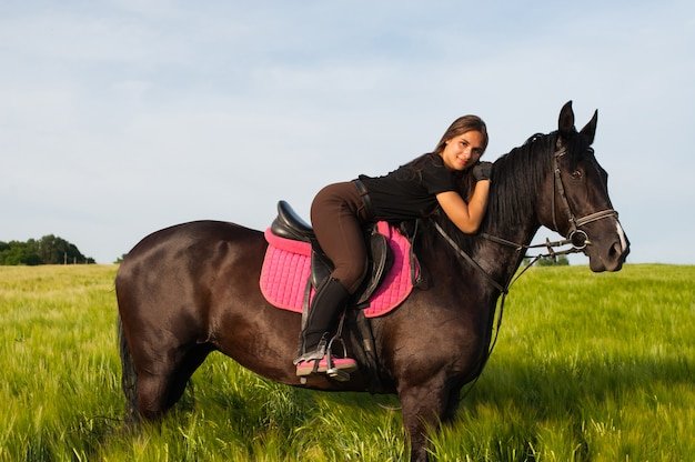 A girl and a young sports horse in the nature