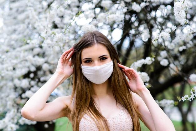 少女、春の庭で彼女の顔に滅菌滅菌マスクの若い女性。大気汚染、ウイルス、パンデミックコロナウイルスの概念。