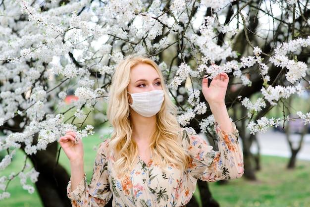 Девушка, молодая женщина в защитной стерильной медицинской маске на лице в весеннем саду. загрязнение воздуха, вирус, концепция пандемии коронавируса.