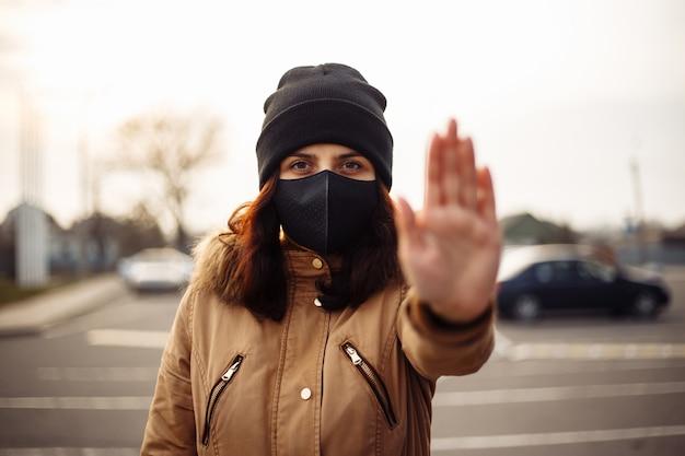 女の子、若い女性は、屋外のカメラを見て、彼女の顔に保護滅菌医療用黒いマスクを着て、街の通りで手のひら、手を示し、兆候を停止しません。汚染、ウイルス、パンデミックコロナウイルスの概念。