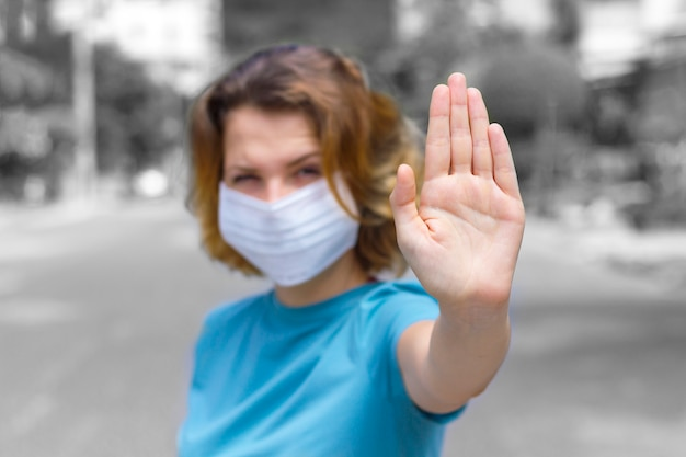 Girl, young woman in protective sterile medical mask on her face outdoors, on asian street show palm, hand, stop no sign. air pollution, virus, chinese pandemic coronavirus concept. focus on hand.
