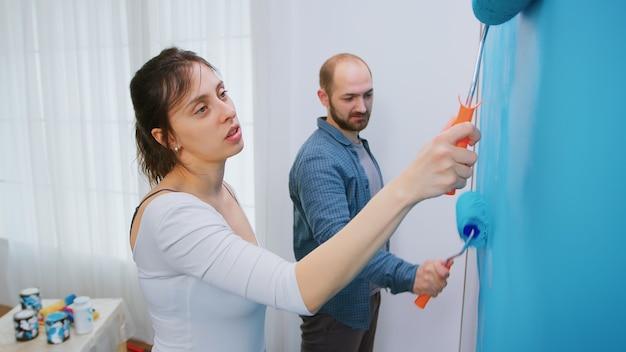 Подруга и парень красят стену синей краской во время переделки гостиной. ремонт квартир и строительство дома одновременно с ремонтом и благоустройством. ремонт и отделка.