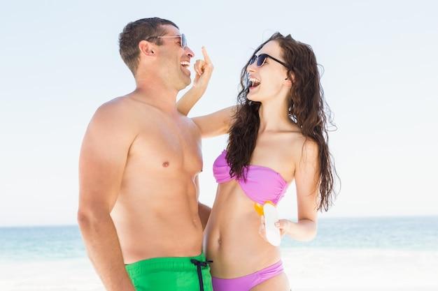 Girlfriend applying sun cream on boyfriend