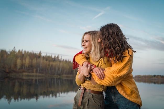 ガールフレンドは自然の中で休んでいます。ライフスタイルを抱きしめて笑っている女の子。