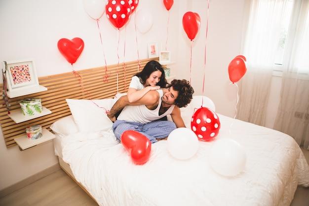 ガールフレンドはベッドの上で彼女のボーイフレンドの背中を登ります