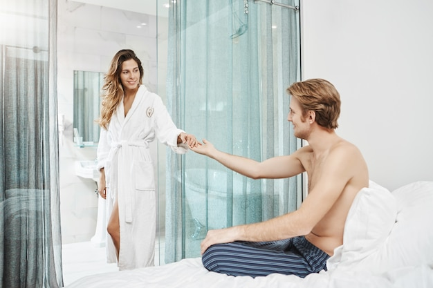 Girlfriend comes from bathroom wearing bathrobe, holding hand that her boyfriend stretches and smiling at him. couple flirts and shares their love being in hotel bedroom.