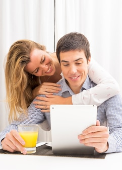 Girlfriend embracing her smiling boyfriend holding glass of juice and digital tablet