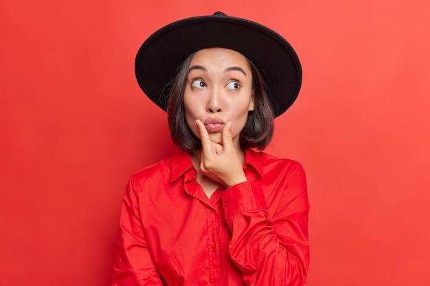 여자친구는 둥근 입술 가까이에 손을 얹고 mwah는 세련된 모자를 쓰고 셔츠는 로맨틱한 분위기를 가지고 있어 밝은 빨간색으로 데이트 포즈를 준비합니다