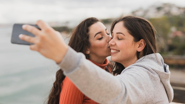 Girlfriend kiss on cheek while taking selfie