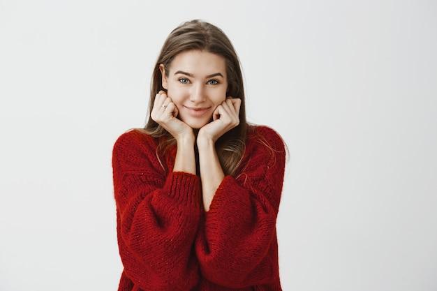 休暇から戻ってきた友人の信じられない話を聞いているガールフレンド。ゆるいセーター、手のひらに頭をもたれ、軽薄な笑顔でうれしそうな魅力的なヨーロッパの女性の屋内撮影