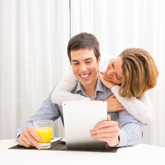 Girlfriend loving her smiling boyfriend holding glass of juice and digital tablet