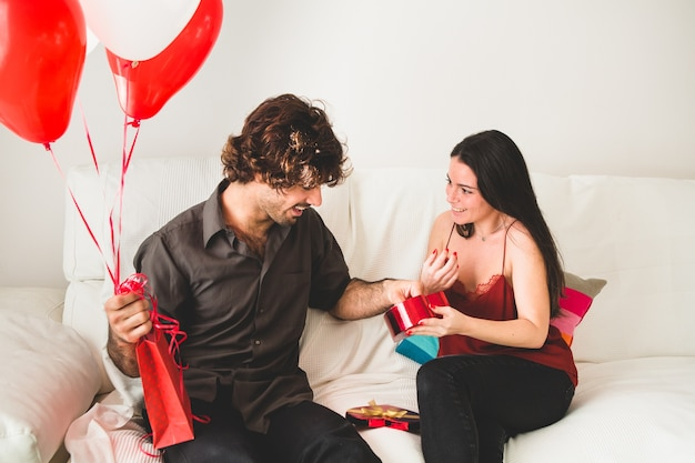Girlfriend offering her boyfriend a candy from a red box