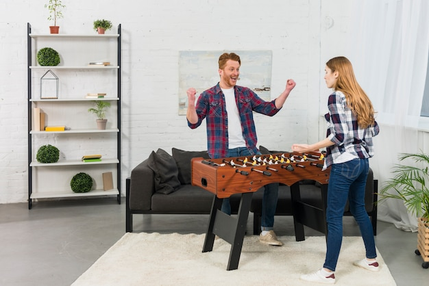 Girlfriend shrugging in front of man celebrating his success near the table soccer at home