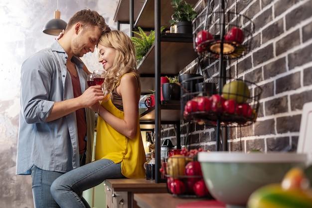 웃는 여자 친구. 그녀의 잘 생긴 남자를 포옹하고 함께 와인을 마시는 동안 웃고있는 blonde-haired 여자 친구