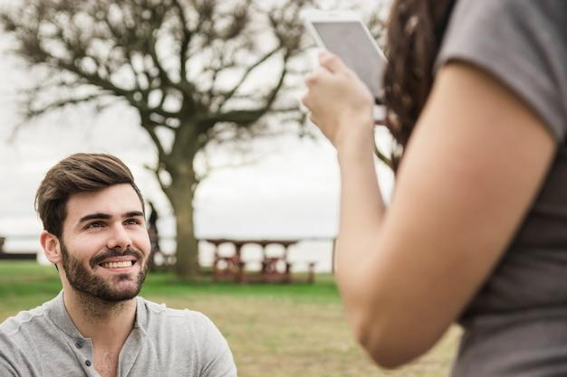 Girlfriend taking photo of her smiling boyfriend on digital tablet in the park