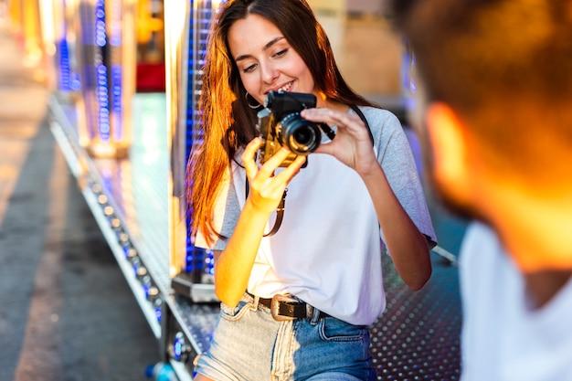 Девушка фотографирует парня на ярмарке