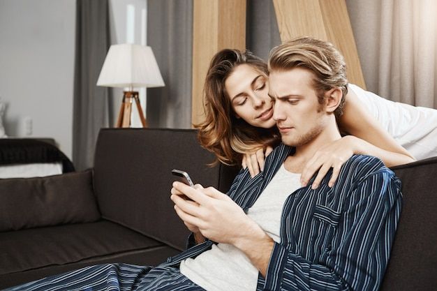 Girlfriend trying to comfort and cheer boyfriend while he sitting gloomy, scrolling feed in smartphone. husband likes playing game in his telephone and not pays attention to wife at all.