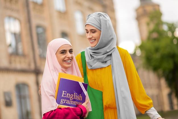 친구와 여자 친구. 친구 근처에 영어 책 서를 들고 분홍색 히잡을 입고 빛나는 학생