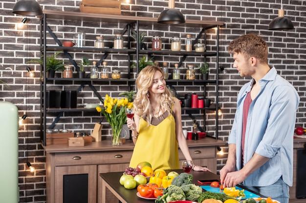 와인과 여자 친구. 와인을 마시고 저녁 식사를 요리하는 남자를 보는 매력적인 행복한 여자 친구를 보내십시오.