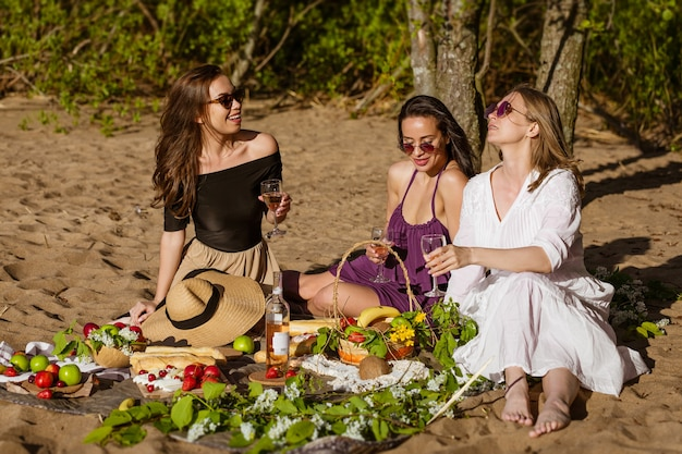 Girlfriends celebrate in the summer at a picnic beautiful women are having fun with alcohol in nature caucasian girls have fun in nature on the shore sitting on a blanket drink wine and eat fruit